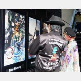 公開初日を迎えたアニメ映画「劇場版『鬼滅の刃』無限列車編」のポスターの写真を撮る人たち(東京・新宿)/(C)共同通信社