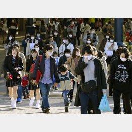 14日、マスクを着けて東京ディズニーランドに向かう人たち(C)共同通信社