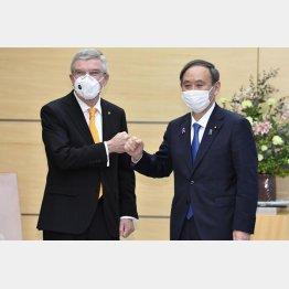 三文芝居(IOCのバッハ会長と会談する菅首相)/(C)共同通信社