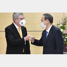 16日、会談を前にIOCのバッハ会長(左)とグータッチをする菅首相(C)共同通信社