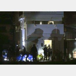 弾痕が確認された現場の建物を調べる兵庫県警の捜査員ら=18日午前2時25分、兵庫県尼崎市(C)共同通信社