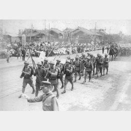 満州事変1周年記念日に、名誉の軍旗を掲げて大阪市内を行進する歩兵第8連隊(1932年9月18日=日本電報通信社撮影)