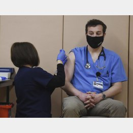 米コロラド州で、新型コロナウイルス感染症ワクチンの接種を受ける医師(右、ERILEE・BENNETT/THE GAXETTE・AP=共同)