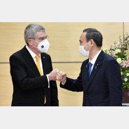 菅首相(右)はIOCのバッハ会長とグータッチしていたが、「デッドライン」はすぐそこ…(C)共同通信社