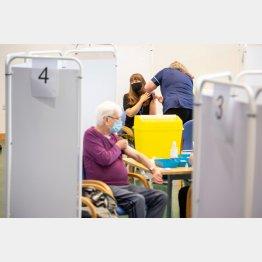 英国のエプソム競馬場のコロナウイルスワクチン接種センターでワクチン接種を受ける人々(C)ロイター