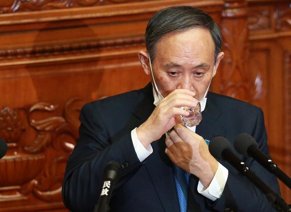 18日衆院本会議、施政方針演説の途中で水を飲む菅首相(C)日刊ゲンダイ