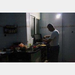 停電中にバッテリーでLEDライトをつけ料理するサミール(2014年)/(撮影)藤原亮司
