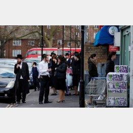 英ロンドン北部スタンフォードヒルの街、店先に集まる正統派ユダヤ教の人たち(C)ロイター