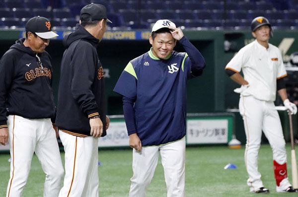 試合前の練習で巨人のコーチに挨拶する田口(中央)/(C)共同通信社