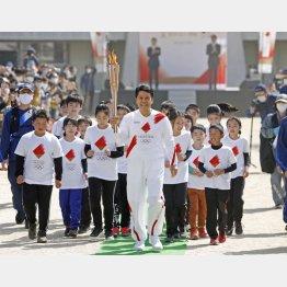 長野県飯田市をスタートする聖火ランナーの峰竜太さんと地元の子どもたち(C)共同通信社
