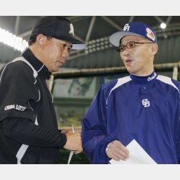 2010年日本シリーズメンバー表を交換するときの筆者と落合さん(C)共同通信社
