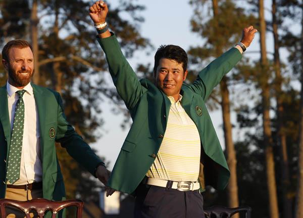 グリーンジャケットを着て勝利を喜ぶ松山(左は前年VのD・ジョンソン)/(C)ロイター