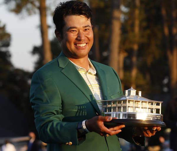 グリーンジャケットを着て、トロフィーを手に笑顔の松山(C)ロイター