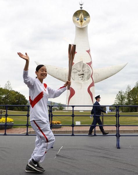 聖火リレーで太陽の塔の前を走る、元トランポリン選手の廣岡遥(C)日刊ゲンダイ