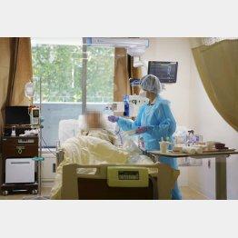 医療現場は逼迫(病床の新型コロナウイルス患者へ食事の介助をする看護師)/(C)共同通信社
