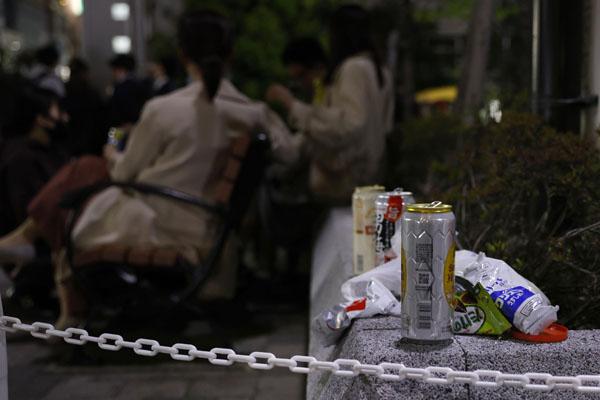 東京・新橋の公園に集まって酒を飲む人たち。手前は置かれた酒の缶など=21日夜(C)共同通信社