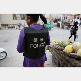 当局から配布された「POLICE」と書かれた防弾衣を着て商売をするウイグルの女性(2018年)/(撮影)川嶋久人