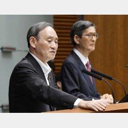 7日、記者会見で質問に答える菅首相。奥は新型コロナウイルス感染症対策分科会の尾身茂会長(C)共同通信社