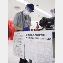 今度こそ、水際対策を徹底しなければ(海外からの入国者の質問票などをチェックする厚労省成田空港検疫所の検疫官)/(C)共同通信社