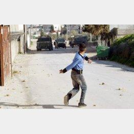 写真②ガザ地区でイスラエル軍に向かって石を投げる若者(C)ロイター
