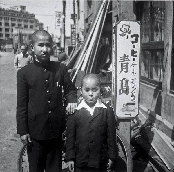 店の前に立つ2代目オーナー城和裕氏の幼少期(提供写真)