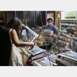 22日、香港の新聞スタンドで蘋果日報を数部購入する女性(C)ゲッティ=共同