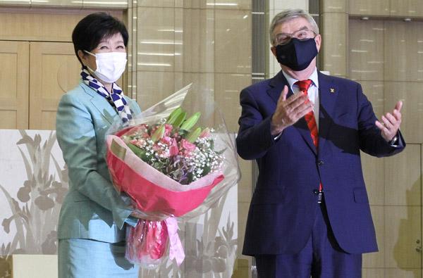 とても五輪どころじゃない(15日、会談を前に、IOCのバッハ会長から花束を受け取る小池百合子都知事)/(C)JMPA