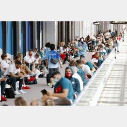海外選手団の入国がピークを迎えた中…(成田空港で検査を待つ選手や関係者たち)/(C)共同通信社