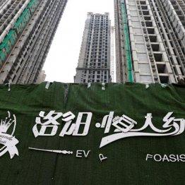 中国恒大集団グループが開発する高層マンションは未完成のままで、看板が剥げちている…